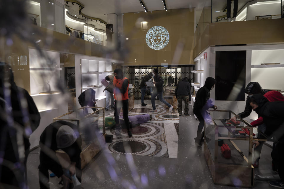 People loot a Versace store during a protest condemning the arrest of rap singer Pablo Hasel in Barcelona, Spain, Saturday, Feb. 20, 2021. The imprisonment of Pablo Hasel for inciting terrorism and refusing to pay a fine after having insulted the country's monarch has triggered a social debate and street protests. (AP Photo/Felipe Dana)