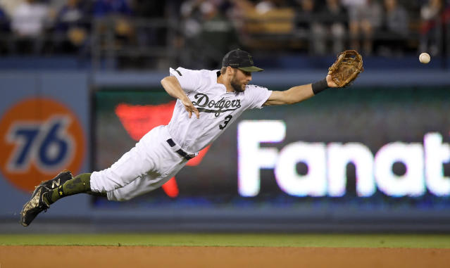 Los Angeles Dodgers shortstop Chris Taylor can't reach a ball hit for an RBI single by San Diego Padres' Jose Pirela during the seventh inning of a baseball game Saturday, May 26, 2018, in Los Angeles. (AP Photo/Mark J. Terrill)