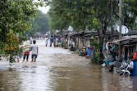 Residents make their way through floodwaters on a street following heavy rains in Hyderabad on October 14, 2020. (Photo by NOAH SEELAM / AFP) (Photo by NOAH SEELAM/AFP via Getty Images)