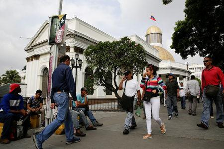 People walk past the building of the National Assembly in Caracas