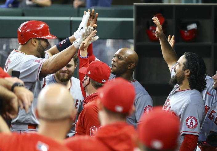 Los Angeles Angels Albert Pujols (5) is greeted in the dugout by Justin Upton, and Anthony Rendon after a solo home run in the third inning against the Texas Rangers during a baseball game on Monday, April 26, 2021, in Arlington, Texas. (AP Photo/Richard W. Rodriguez)