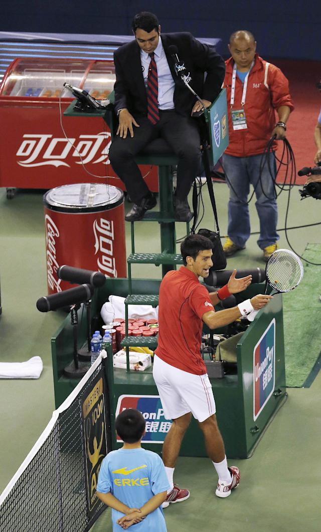 Serbia's Novak Djokovic, bottom, reacts to tournament referee, top, after missing a point against France's Jo-Wilfried Tsonga during the singles semifinal match of the Shanghai Masters tennis tournament at Qizhong Forest Sports City Tennis Center in Shanghai, China, Saturday, Oct. 12, 2013. Djokovic won 6-2, 7-5. (AP Photo/Eugene Hoshiko)