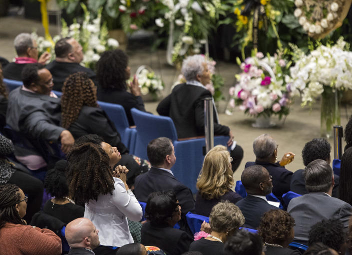 """A woman stands during the memorial service for NASA mathematician Katherine Johnson on Saturday, March 7, 2020, at Hampton University Convocation Center in Hampton, Va. Johnson, a mathematician who calculated rocket trajectories and earth orbits for NASA's early space missions and was later portrayed in the 2016 hit film """"Hidden Figures,"""" about pioneering black female aerospace workers died on Monday, Feb. 24, 2020. She was 101. (Kaitlin McKeown /The Virginian-Pilot via AP)"""