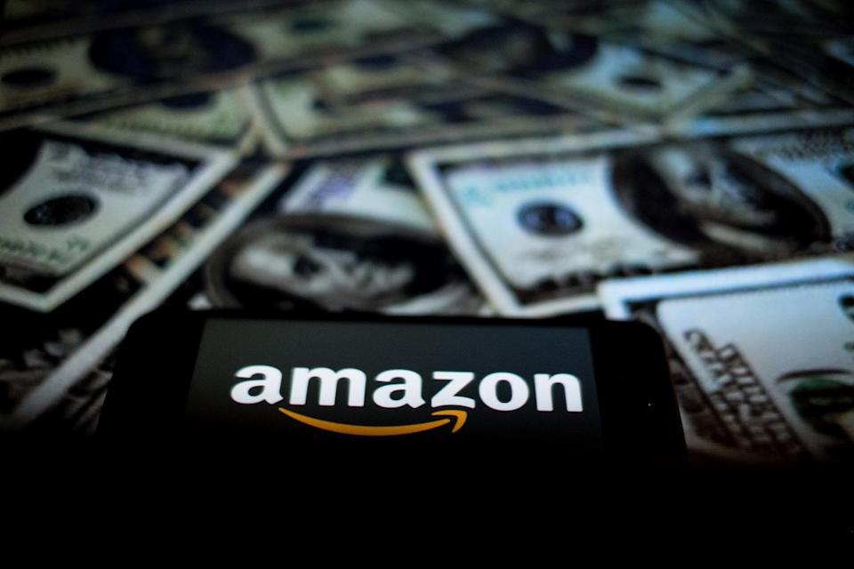 In this photographic illustration, the Amazon logo is displayed on the screen of a smartphone as a background to the Dollars on a computer person   on April 29, 2021 in Rome, Italy. (Photo by Andrea Ronchini/NurPhoto)
