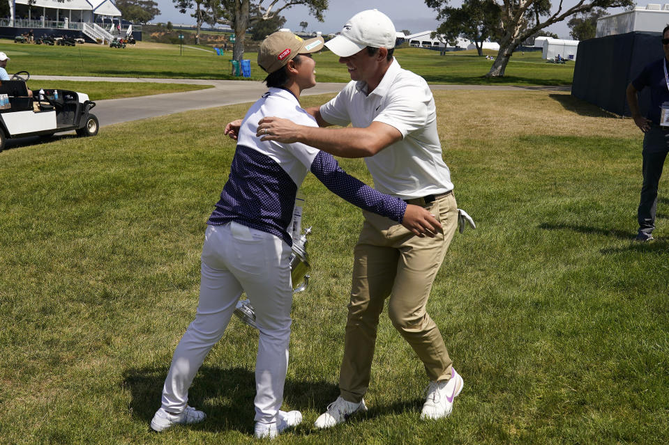 Rory McIlroy, of Northern Ireland, right, greets 2021 U.S. Women's Open golf champion Yuka Saso, of the Philippines, during a practice round of the U.S. Open Golf Championship, Tuesday, June 15, 2021, at Torrey Pines Golf Course in San Diego. (AP Photo/Gregory Bull)