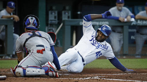 Kansas City Royals' Abraham Almonte (45) beats the tag by Texas Rangers catcher Robinson Chirinos to score on a double by Adalberto Mondesi during the third inning of a baseball game Monday, June 18, 2018, in Kansas City, Mo. (AP Photo/Charlie Riedel)