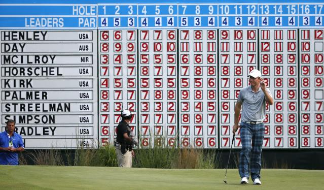 Russell Henley, right, holds up his ball after putting on the 18th hole during the third round of the Deutsche Bank Championship golf tournament in Norton, Mass., Sunday, Aug. 31, 2014. (AP Photo/Michael Dwyer)