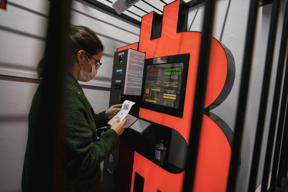 BARCELONA, SPAIN - JANUARY 29: A woman uses a Bitcoin ATM machine placed within a safety cage on January 29, 2021 in Barcelona, Spain. The European Union Agency for Law Enforcement Cooperation (Europol) and local law enforcement busted an allegedly fraudulent scam posing as a firm that specialized in cryptocurrency and foreign exchange investment training out of Andorra. (Photo by Cesc Maymo/Getty Images)