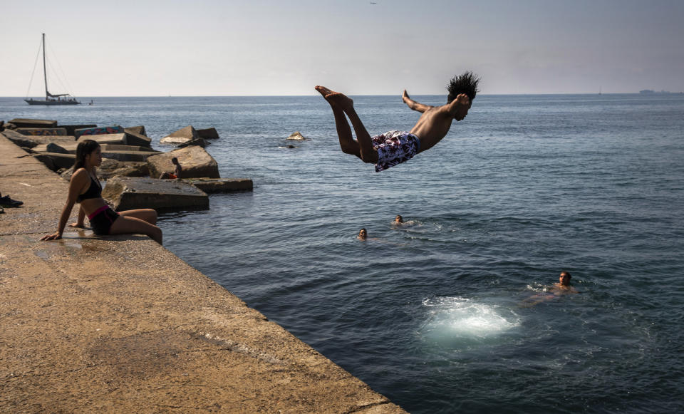 A boy jumps into the water at the beach in Barcelona, Spain, Thursday, July 25, 2019. Parts of Europe saw record-high temperatures on Thursday as much of the continent was trapped in a heat wave, the second in two months. (AP Photo/Emilio Morenatti)
