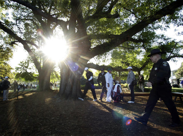 <p>Tiger Woods, center, is escorted by security personnel as he heads to his practice round for the Masters golf tournament at the Augusta National Golf Club in Augusta, Ga., Wednesday, April 8, 2009. (AP Photo/David J. Phillip) </p>