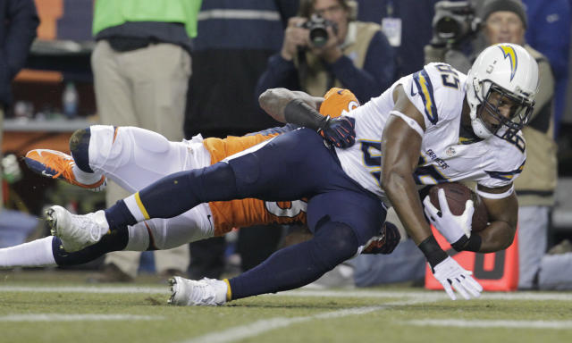 San Diego Chargers tight end Antonio Gates (85) is tackled by a Denver Broncos defender during the first quarter of an NFL football game, Thursday, Dec. 12, 2013, in Denver. (AP Photo/Joe Mahoney)