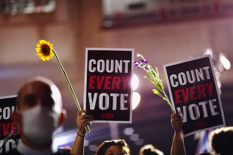 """Activists hold up flowers and signs stating """"COUNT EVERY VOTE"""" across the street from where votes are still being counted, two days after the 2020 U.S. presidential election, in Philadelphia"""