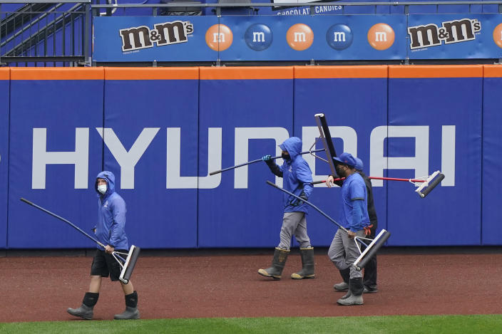 Groundskeepers make their way on the warning track before a a baseball game between the New York Mets and the Atlanta Braves was postponed due to rain, Sunday, May 30, 2021, in New York. It was the third rainout in five days for the Mets. (AP Photo/Kathy Willens)