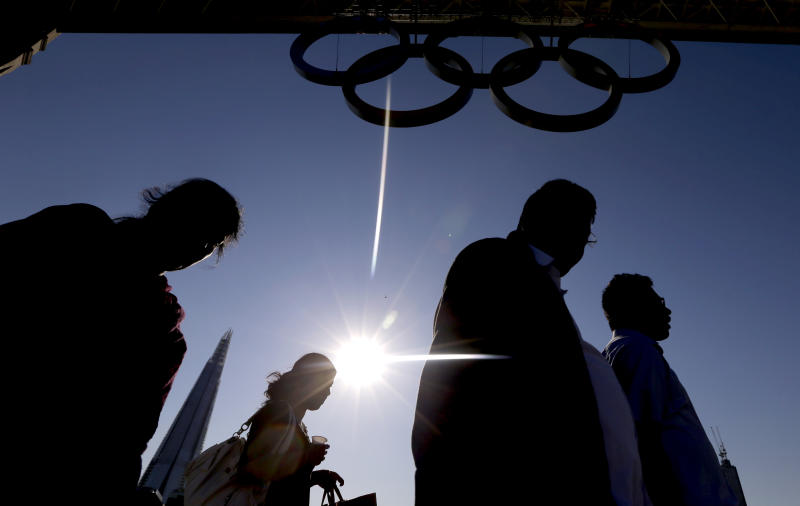 Commuters are silhouetted as they cross Tower Bridge in front of Olympic rings in London, Monday, July 23, 2012. The summer Olympics in London will start on Friday July 27. (AP Photo/Kirsty Wigglesworth)