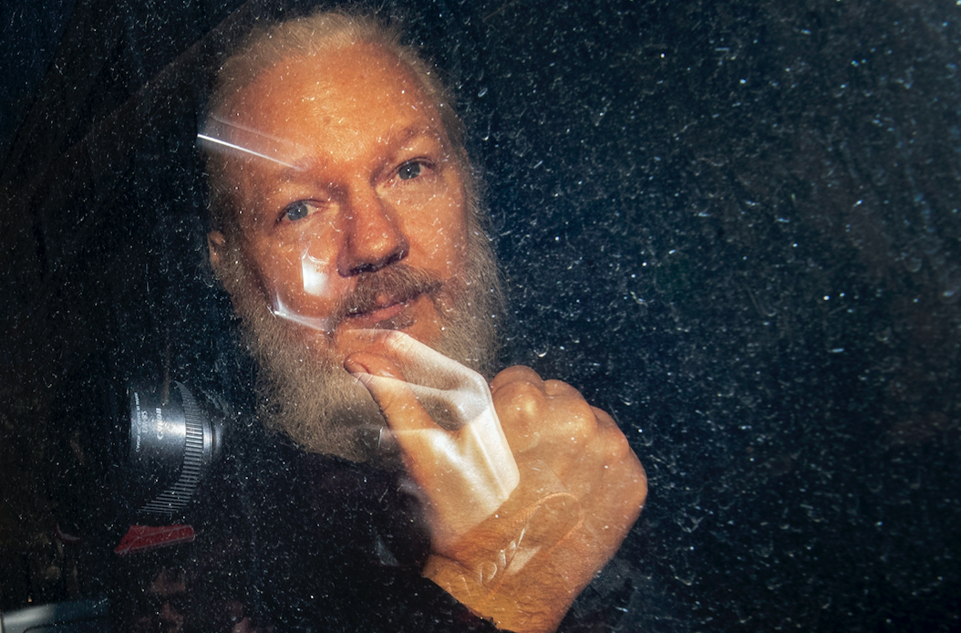 <em>Assange gives a thumbs up to photographers following his arrest (PA)</em>