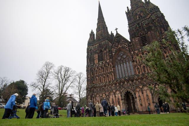 Members of the public queue outside Lichfield Cathedral, Staffordshire, to receive an injection of the Oxford/AstraZeneca coronavirus vaccine (Jacob King/AP)
