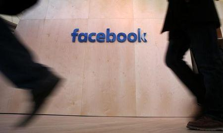 People walk in front of the Facebook logo at the new Facebook Innovation Hub during a preview media tour in BerlinInnovation Hub during a preview media tour in Berlin