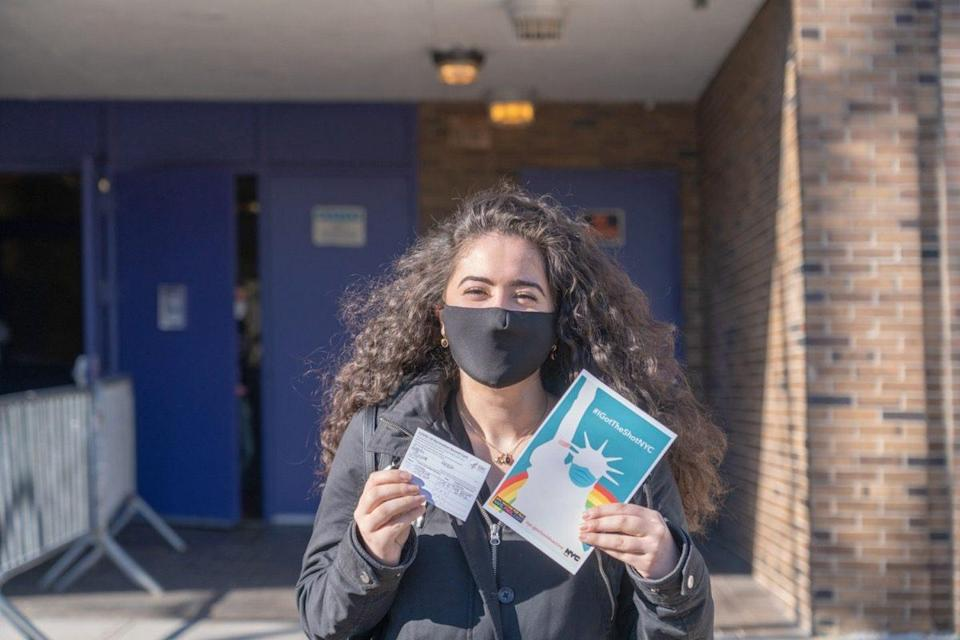 """A woman displays her vaccination card and the """"IGotTheShotNYC"""" banner after exiting the NYC Health Department Vaccine Hub at Hillcrest High School in Queens"""