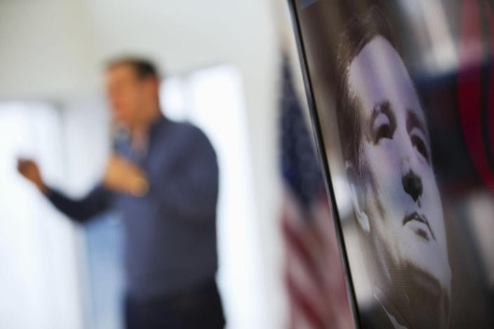 <p>An image of Republican presidential candidate, Sen. Ted Cruz, R-Texas, is displayed on a monitor as he speaks in the background during a campaign event at a Toyota auto dealership, Thursday, Feb. 4, 2016, in Portsmouth. <i>(Photo: David Goldman/AP)</i></p>