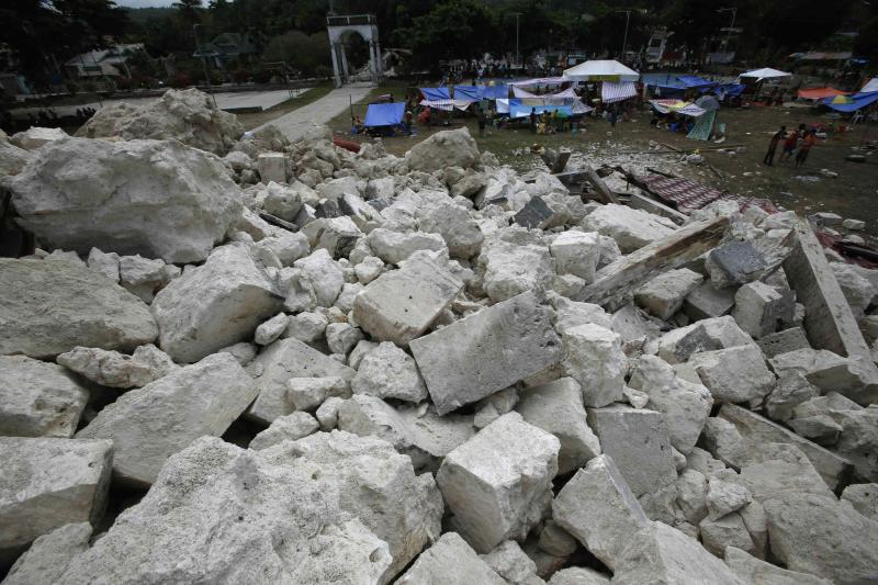 Residents stay in makeshift shelters in front of a heap of rubble from the collapsed Our Lady of Light church in Loon