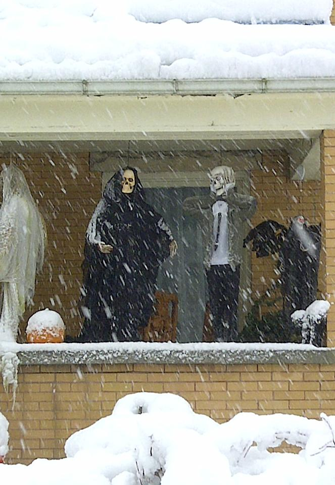 Halloween decorations are seen during a snowstorm, Tuesday, Oct. 30, 2012, in Elkins, W.Va. Superstorm Sandy buried parts of West Virginia under more than a foot of snow on Tuesday, cutting power to at least 243,000 customers and closing dozens of roads. At least one death was reported. (AP Photo/Vicki Smith)