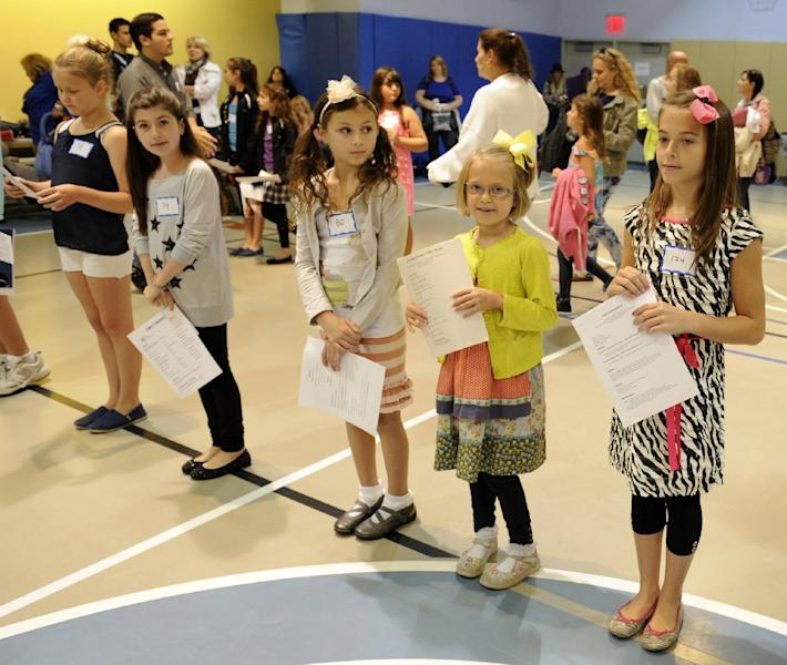 """This Sept. 15, 2013 image released by NBC shows a row of hopefuls at an open casting call for the Von Trapp children in NBC's """"The Sound of Music,"""" at Grace Church School in New York. A remake of the 1965 film classic and the original 1959 Broadway production, starring Carrie Underwood and Stephen Moyer, will air on Dec. 5. (AP Photo/NBC, Virginia Sherwood)"""