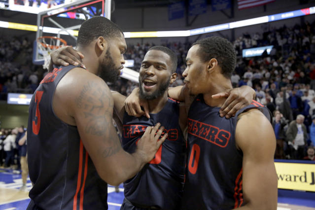 Dayton's Jalen Crutcher, center, is congratulated by teammates Trey Landers, left, and Rodney Chatman after hitting a shot with less than a second left in overtime to defeat Saint Louis 78-76 in an NCAA college basketball game Friday, Jan. 17, 2020, in St. Louis. (AP Photo/Jeff Roberson)