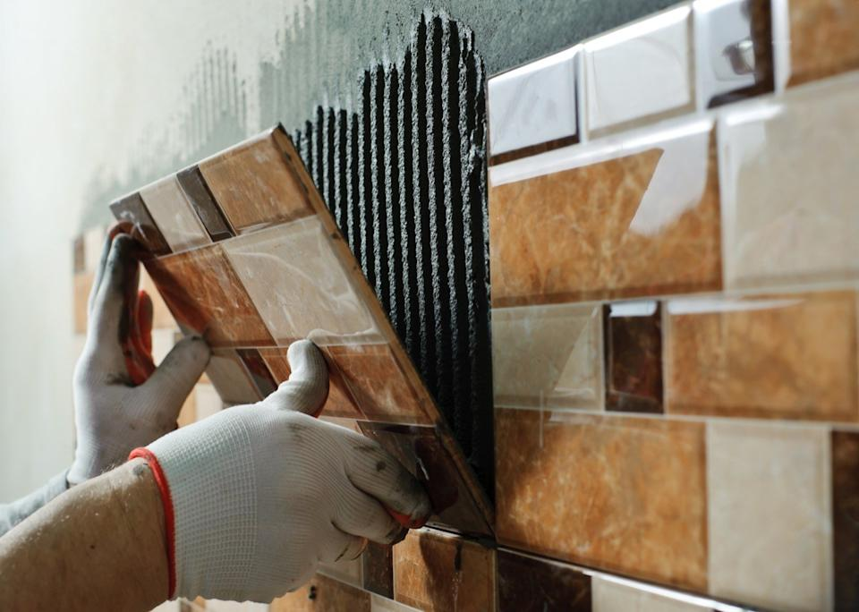 Man laying ceramic tile on the wall