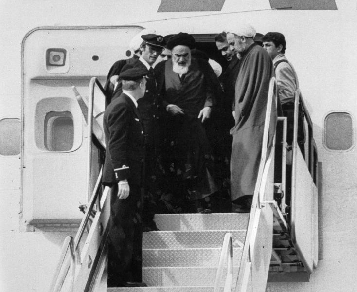 FILE - In this Feb. 1, 1979 file photo, Ayatollah Ruhollah Khomeini, Iran's exiled religious leader, emerges from a plane after his arrival at Mehrabad airport in Tehran, Iran. Friday, Feb. 1, 2019, marks the 40th anniversary of Khomeini's descent from the chartered Air France Boeing 747, a moment that changed the country's history for decades to come. (AP Photo/FY, File)