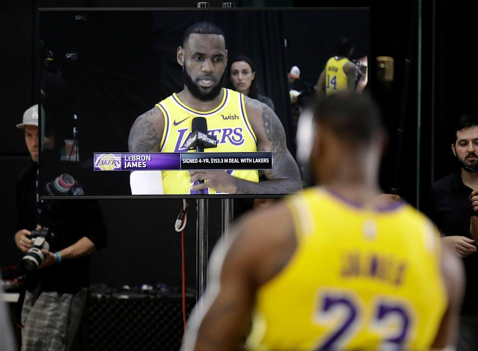 Los Angeles Lakers' LeBron James appears on a television screen as he answers questions during media day at the NBA basketball team's practice facility Monday, Sept. 24, 2018, in El Segundo, Calif. (AP Photo/Marcio Jose Sanchez)