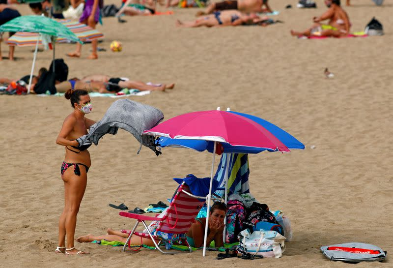 FILE PHOTO: A woman wearing a protective mask is seen on the beach, during the spread of the coronavirus disease (COVID-19) pandemic, in Las Palmas