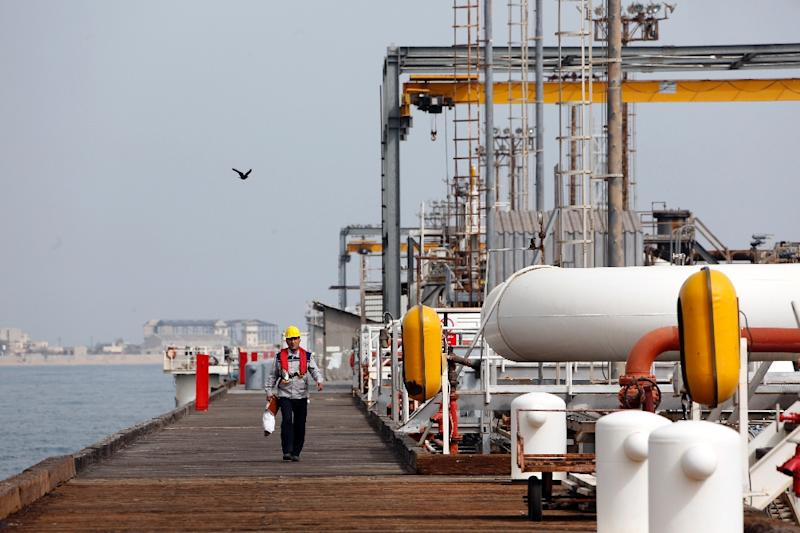 An Iranian labourer walks the platform of an oil facility on Khark Island, on the shore of the Gulf. Iran has signed a deal with French energy giant Total that will lead to a 20-year, $4.9 billion project to develop an offshore gas field (AFP Photo/ATTA KENARE)
