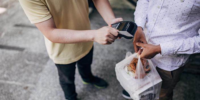 Paying takeout food with credit card (Getty Images stock)