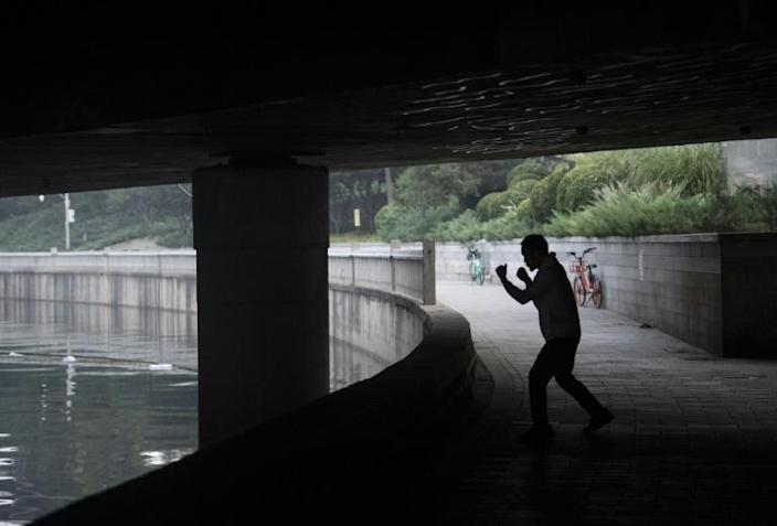 Boxer and food deliveryman Zhang Fangyong shadow boxes under a bridge during a morning run in Beijing (AFP Photo/NOEL CELIS)