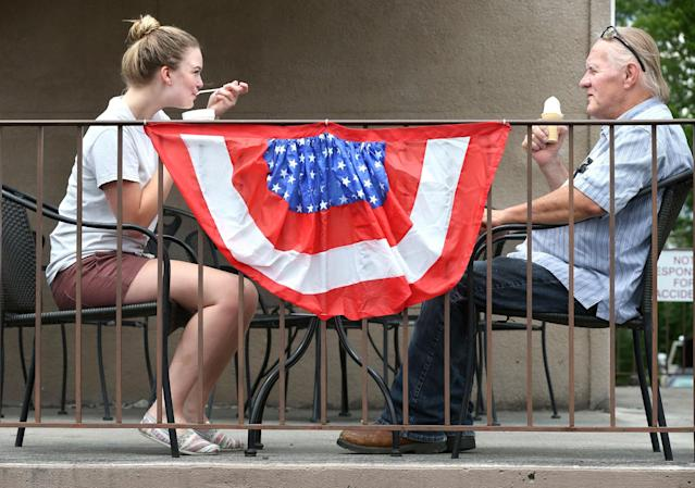 <p>Alexis Mathias of Strasburg, Va. and Dennis Carlyle of Middletown, Va. enjoy a frozen treat at Scoops and Swirls ice cream shop in Middletown, Va. Saturday, July 1, 2017. Much of the town has been decorated by business owners and homeowners for their July 4 parade and fireworks display. (Photo: Jeff Taylor/The Winchester Star via AP) </p>