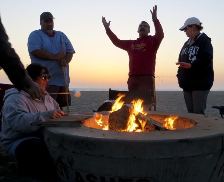 Pamela Abderhalden, from left, and her husband Joe and James and Maria Bleemers, relax around a fire pit at Bolsa Chica State Beach Saturday, April 27, 2013 in Huntington Beach, Calif. Air quality regulators are considering a proposal to ban beach bonfires in Southern California due to health concerns. (AP Photo/Chris Carlson)