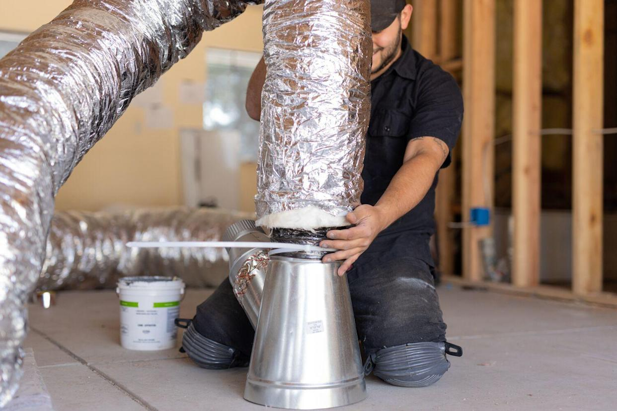 man working on HVAC duct system