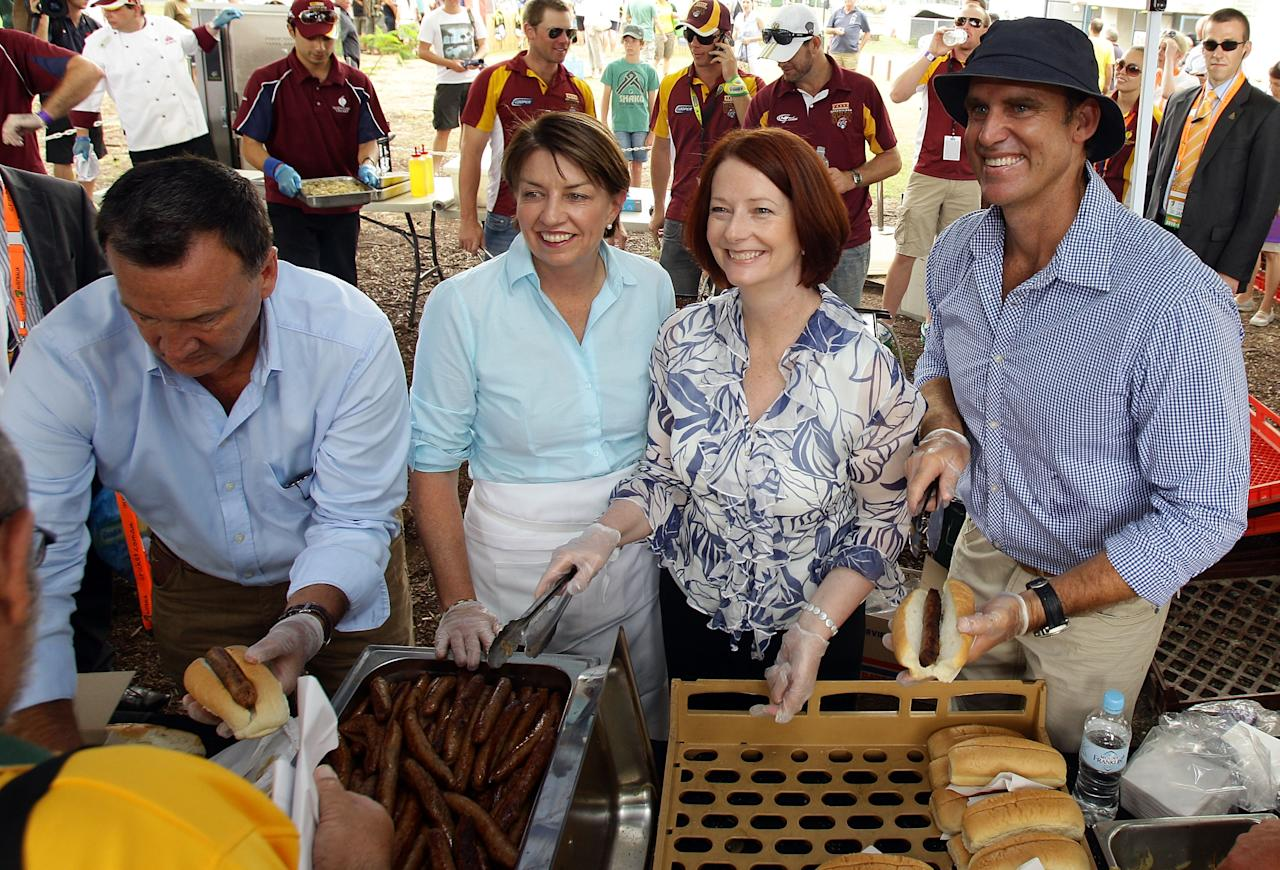 BRISBANE, AUSTRALIA - JANUARY 30:  (L-R) Queensland Premier Anna Bligh, Prime Minister Julia Gillard and former Australian cricketer Matthew Hayden serve up patrons at a free barbeque to raise money for the Queensland flood appeal before game four of the Commonwealth Bank One Day International Series between Australia and England at The Gabba on January 30, 2011 in Brisbane, Australia.  (Photo by Bradley Kanaris/Getty Images)