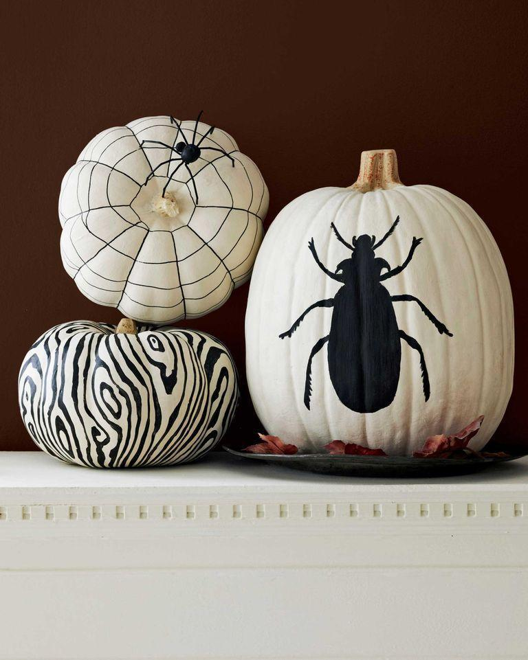 """<p>Stylist Liz Demos loves nothing more than graphic pumpkin designs. She started these with a coat of white flat acrylic craft paint. After allowing 20 minutes to dry, a black paint pen and black flat acrylic craft paint was used to create the bold designs. <br></p><p><em><a href=""""https://www.countryliving.com/diy-crafts/how-to/a3032/pumpkin-painting-1009/"""" rel=""""nofollow noopener"""" target=""""_blank"""" data-ylk=""""slk:Get the tutorial>>"""" class=""""link rapid-noclick-resp"""">Get the tutorial>></a></em><a href=""""https://www.amazon.com/Liquitex-BASICS-Acrylic-Paint-Black/dp/B0014ZNJVW?"""" rel=""""nofollow noopener"""" target=""""_blank"""" data-ylk=""""slk:"""" class=""""link rapid-noclick-resp""""><br></a></p><p><a class=""""link rapid-noclick-resp"""" href=""""https://www.amazon.com/Liquitex-BASICS-Acrylic-Paint-Black/dp/B0014ZNJVW?tag=syn-yahoo-20&ascsubtag=%5Bartid%7C10055.g.33437890%5Bsrc%7Cyahoo-us"""" rel=""""nofollow noopener"""" target=""""_blank"""" data-ylk=""""slk:SHOP BLACK PAINT"""">SHOP BLACK PAINT </a><br></p>"""