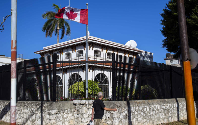 FILE - In this April 17, 2018 file photo, a man walks beside Canada's embassy in Havana, Cuba. Some Canadian diplomats who became mysteriously ill while posted to Cuba are suing the Canadian government. Canada has confirmed 14 cases of unexplained health problems since early 2017. Twenty-six workers at the U.S. Embassy in Cuba have also been affected, suffering a range of symptoms and diagnoses including mild traumatic brain injury, also known as a concussion. Five Canadian diplomats say in a 28 million Canadian dollar ($21 million) lawsuit that the government failed to protect them, hid crucial information and downplayed the seriousness of the risks. (AP Photo/Desmond Boylan, File)