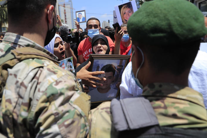 Families of the victims of last year's massive blast at Beirut's seaport, holds their relatives portraits and shout slogans as they banned by Lebanese army soldiers to reach the tightly-secured residents of parliament speaker Nabih Berri, in Beirut, Lebanon, Friday, July 9, 2021. The protest came after last week's decision by the judge to pursue senior politicians and former and current security chiefs in the case, and requested permission for their prosecution. AP Photo/Hussein Malla)