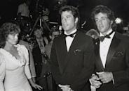 <p>Actress Marilu Henner stands aside as John Travolta and Sylvester Stallone pose together at the <em>Stayin' Alive</em> premiere in 1983.</p>