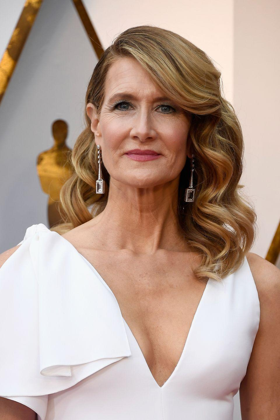 <p>If you've always wanted bangs but aren't <em>quite</em> ready to make the commitment to having them in your face all the time, try bangs that sweep off to one side. Style the rest of your hair asymmetrically and wavy for a beautiful Laura Dern-inspired look.</p>