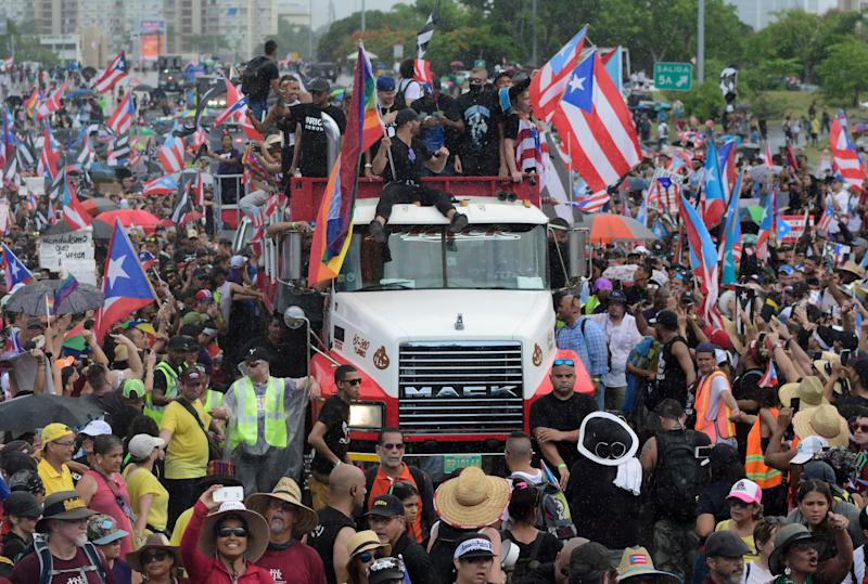 Puerto Rican singer Ricky Martin, front atop truck, participates with other local celebrities in the protest.