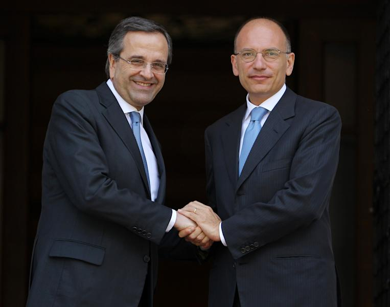 Greece's Prime Minister Antonis Samaras, left, welcomes his Italian counterpart Enrico Letta at the Maximos Mansion in Athens, Monday, July 29, 2013. Letta in his two-day working visit with his Greek counterpart will hold talks for the youth unemployment, illegal immigration and the Trans Adriatic Pipeline (TAP). (AP Photo/Thanassis Stavrakis)