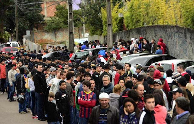 People wait to enter the Atletico Paranaense training center to watch Spain's national soccer team practice session, in Curitiba, Brazil, Tuesday, June 10, 2014. Spain will play in group B of the Brazil 2014 soccer World Cup. (AP Photo/Manu Fernandez)
