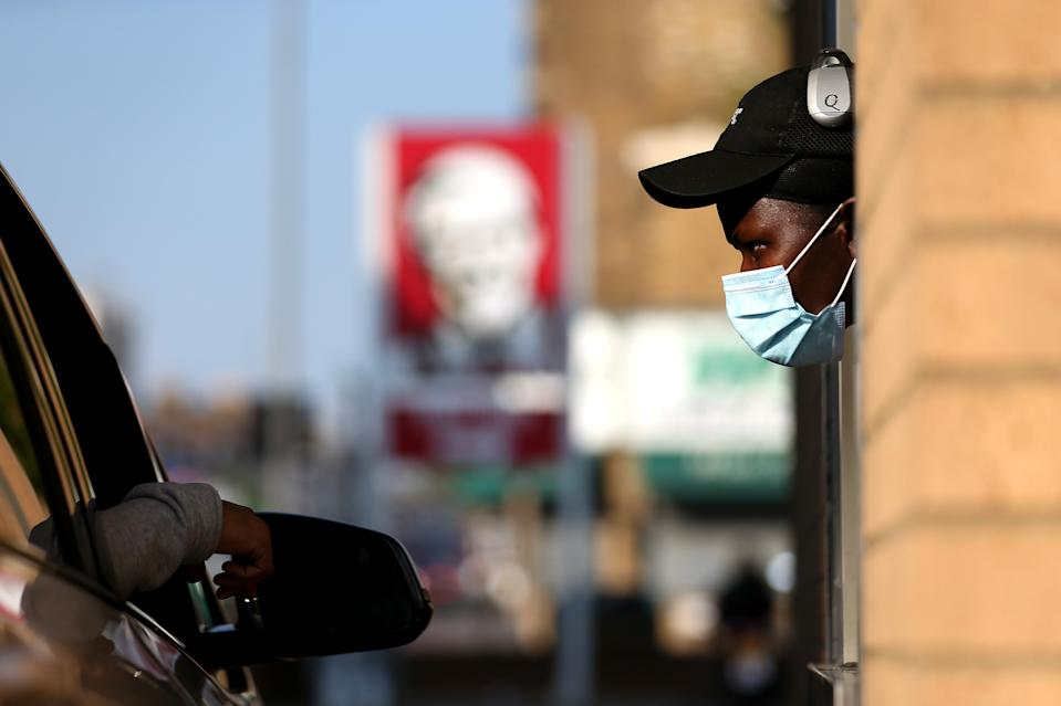LONDON, UNITED KINGDOM - MAY 04: A worker speaks to a customer at KFC as it re-opens for Drive-Thru at a branch in Leyton on May 04, 2020 in London, United Kingdom. The country continued quarantine measures intended to curb the spread of Covid-19, but the infection rate is falling, and government officials are discussing the terms under which it would ease the lockdown. (Photo by Alex Pantling/Getty Images)