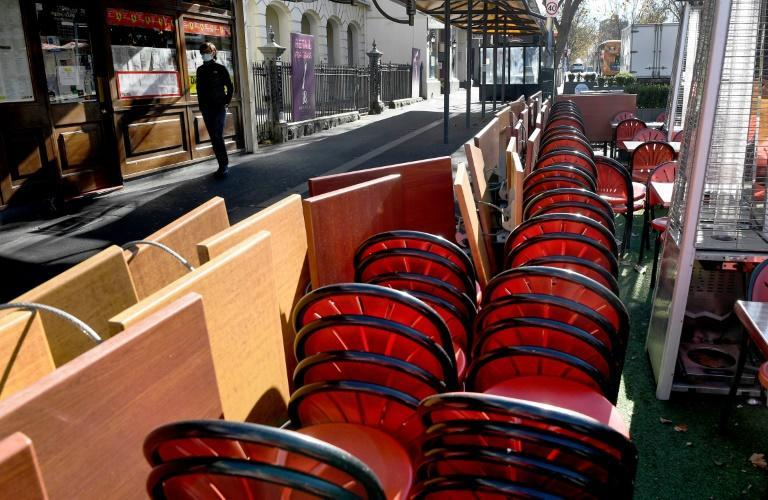 Tables and chairs are stacked up on the Lygon Street cafe and restaurant strip in Melbourne