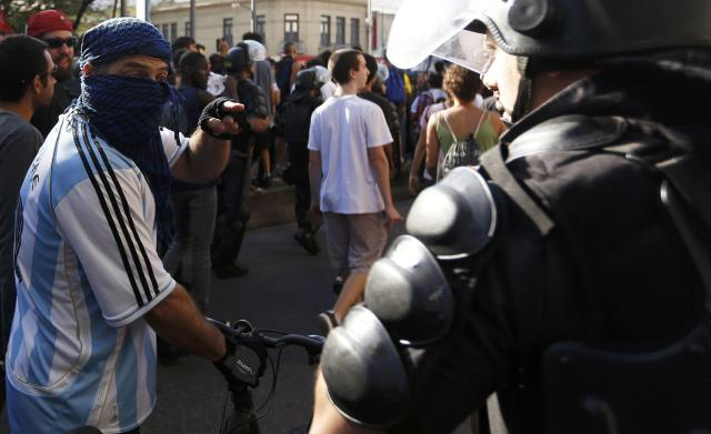 A demonstrator wears an Argentina national team jersey as he argues with a policeman before the 2014 World Cup final match between Argentina and Germany in Rio de Janeiro, July 13, 2014. REUTERS/Marco Bello (BRAZIL - Tags: POLITICS SOCCER CRIME LAW SPORT CIVIL UNREST WORLD CUP)