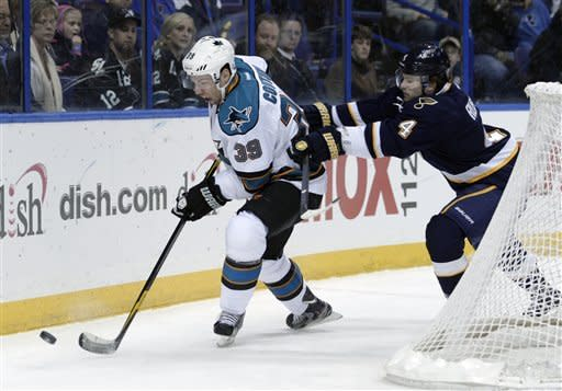 San Jose Sharks' Logan Couture (39) controls the puck as St. Louis Blues' Kris Russell (4) pursues him during the first period of an NHL hockey game Sunday, Feb. 12, 2012, in St. Louis. (AP Photo/Tom Gannam)